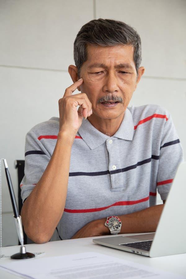 Olhar superior do homem de negócios de Ásia no portátil e no pensamento fotografia de stock