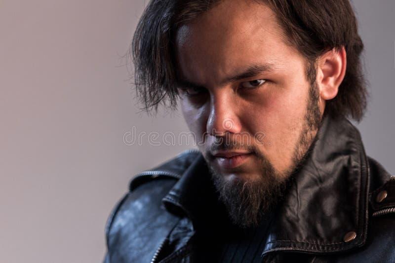 Olhar terrível do indivíduo com uma barba em um casaco de cabedal preto Retrato de um homem em uma rocha ou em um estilo do motoc foto de stock royalty free