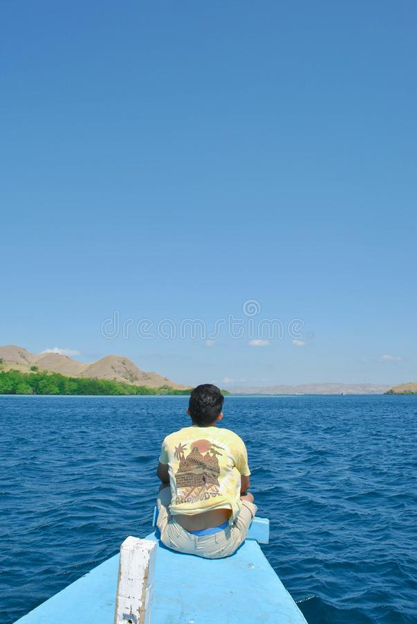Olhares atrás de um homem novo que senta-se em um navio no mar em torno da ilha de Komodo imagens de stock royalty free