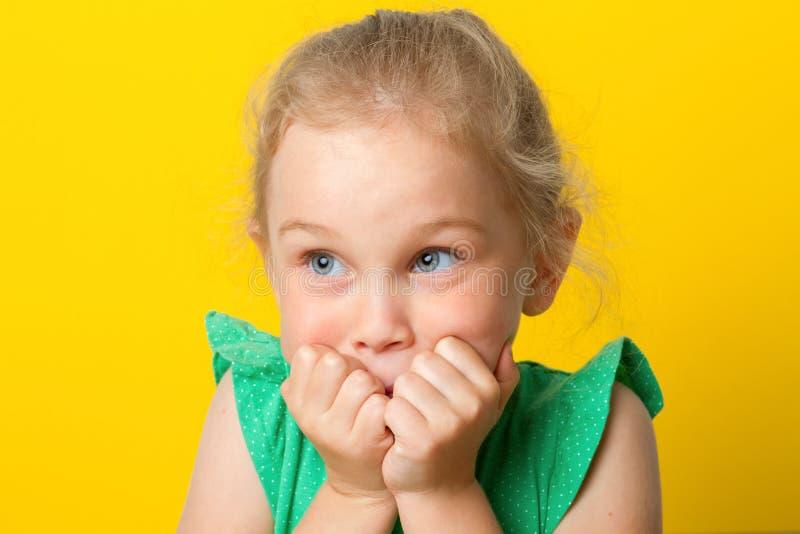 Olhares da menina chocados na câmera No fundo branco fotografia de stock