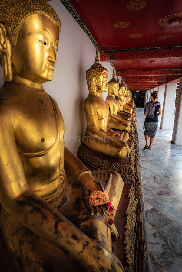 Olhares do turista na fileira de estátuas douradas Wat Pho Palace Thailand Bangkok da Buda fotografia de stock