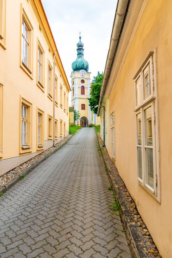Olhe à igreja em Vranov, república checa Vista da rua estreita à construção católica velha foto de stock royalty free