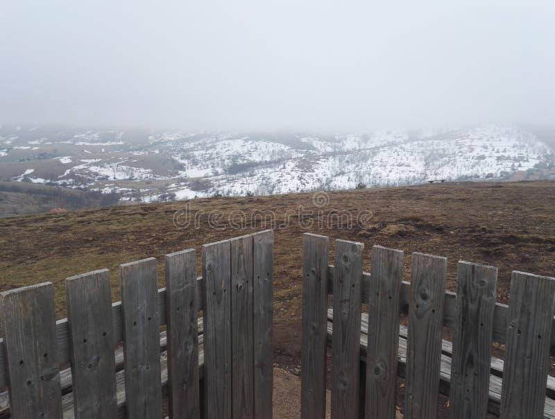 Olhe às montanhas cobertas na neve, céu nevoento foto de stock royalty free