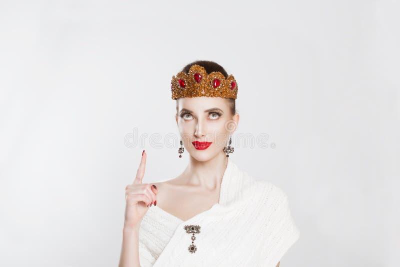 Olhe aqui Uma mulher muito alegre a gestar com o dedo indicador e a aparecer com um aha, eu descobri isto através de gesto manual imagem de stock royalty free
