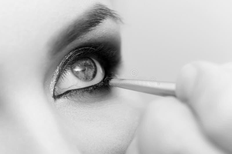 Olho da mulher que obtém a composição que contorna com sombra e a escova pretas imagens de stock royalty free