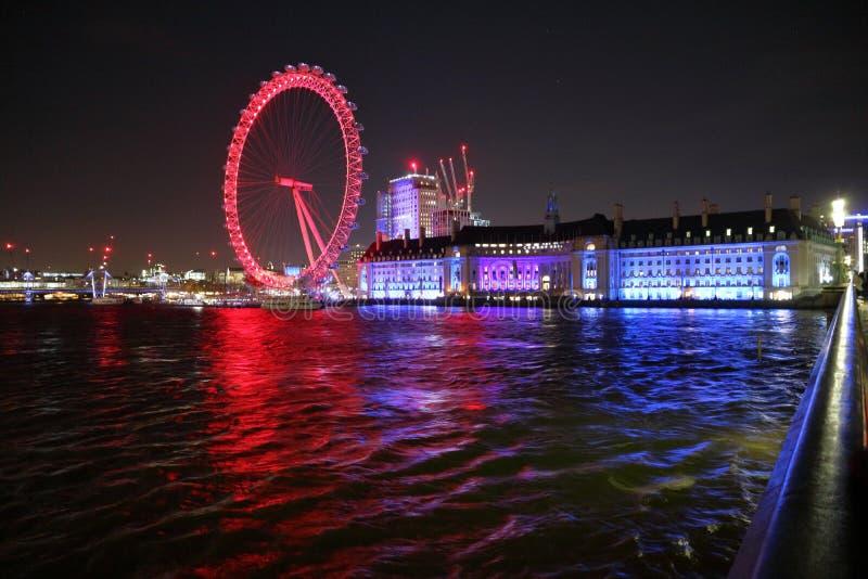 Olho de Londres na noite do cais de Westminster fotografia de stock royalty free