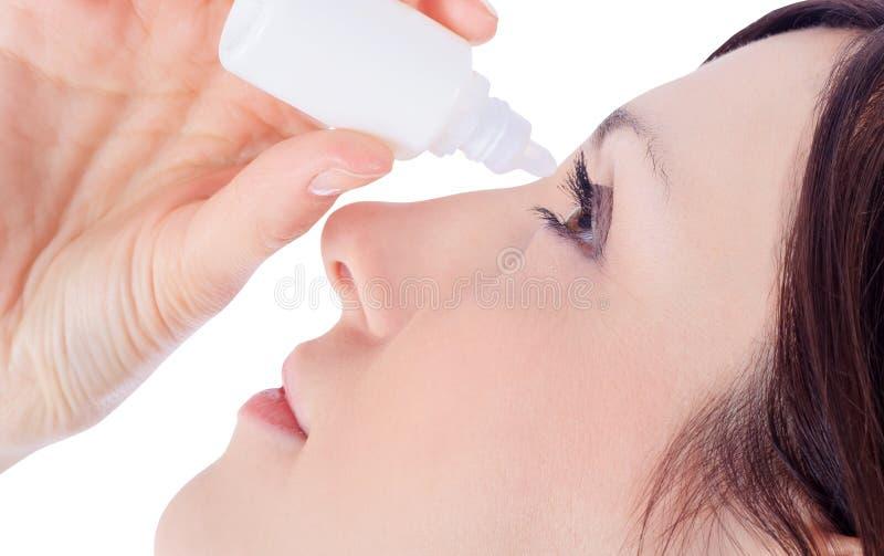 Olho do gotejamento da mulher com gotas de olhos imagens de stock