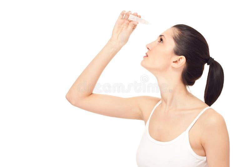 Olho do gotejamento da mulher com gotas de olhos fotos de stock royalty free
