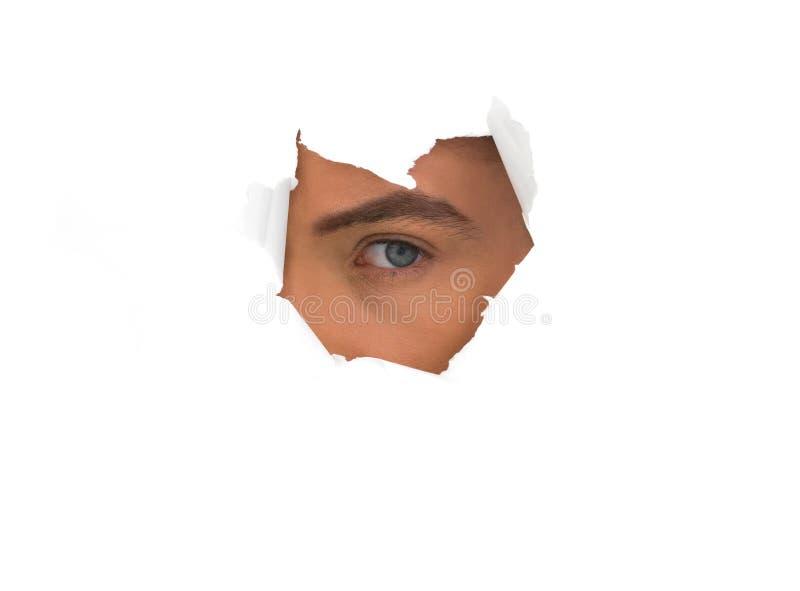Olho do homem no furo de papel foto de stock royalty free