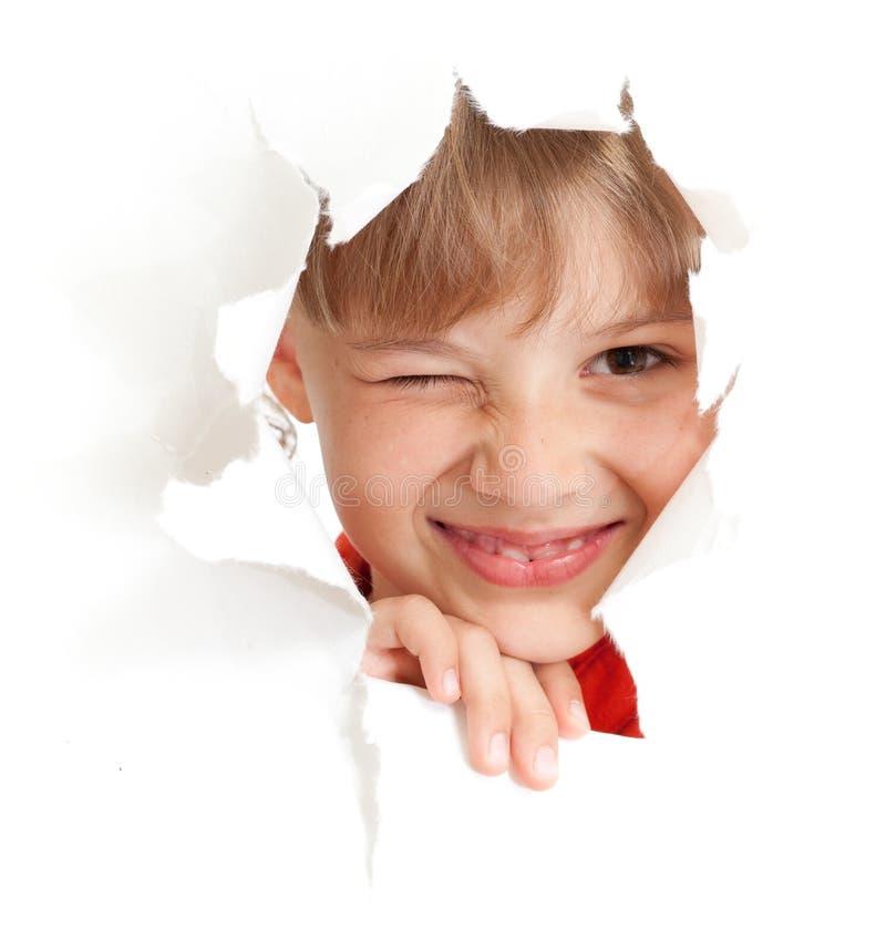 Olho engraçado da piscadela do miúdo no furo de papel rasgado isolado imagem de stock
