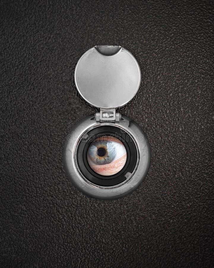 Olho humano no furo da espreitadela fotografia de stock