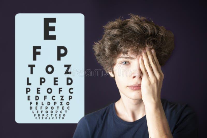 Olho masculino novo da visão e da tampa do olho do teste com mão b imagens de stock