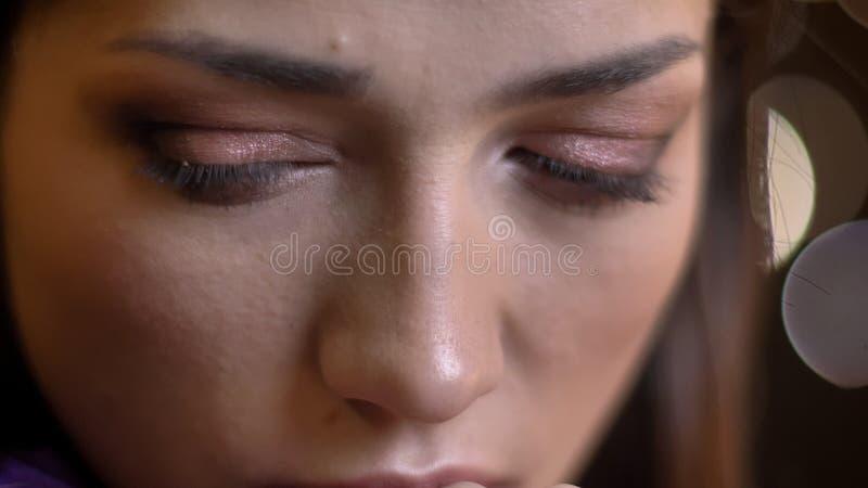 Olho-retrato do close-up de encantar a menina moreno caucasiano que olha para baixo no fundo borrado das luzes imagens de stock
