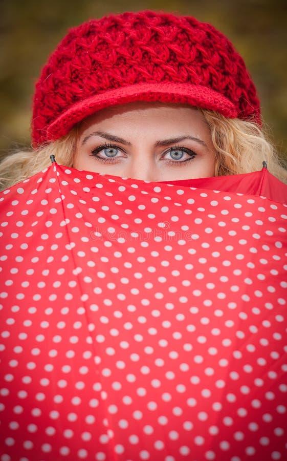 Olhos azuis bonitos sobre o guarda-chuva colorido. A menina loura atrativa com o tampão vermelho que olha sobre o guarda-chuva ver imagens de stock