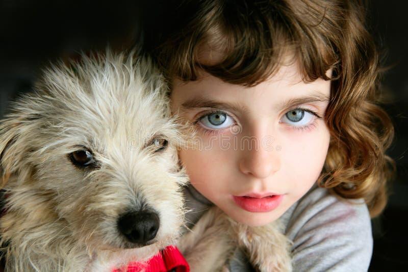 Olhos azuis do retrato do hug do animal de estimação e da menina foto de stock