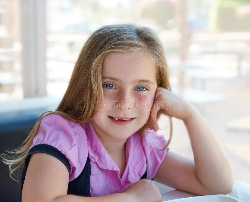 Olhos azuis felizes relaxado louros da expressão da menina da criança fotografia de stock