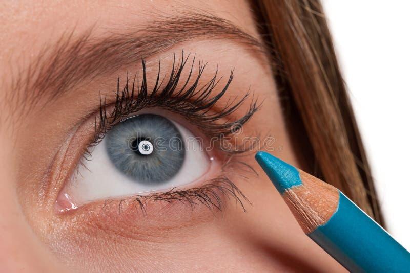Olhos azuis, mulher que aplica o lápis da composição do turqouise imagens de stock