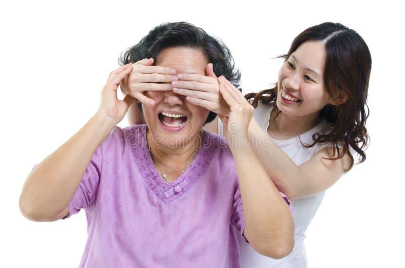 Olhos da mãe da coberta da filha imagem de stock