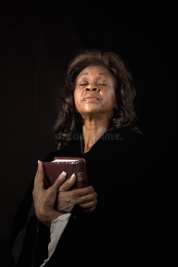 Olhos da mulher fechados com a Bíblia foto de stock royalty free