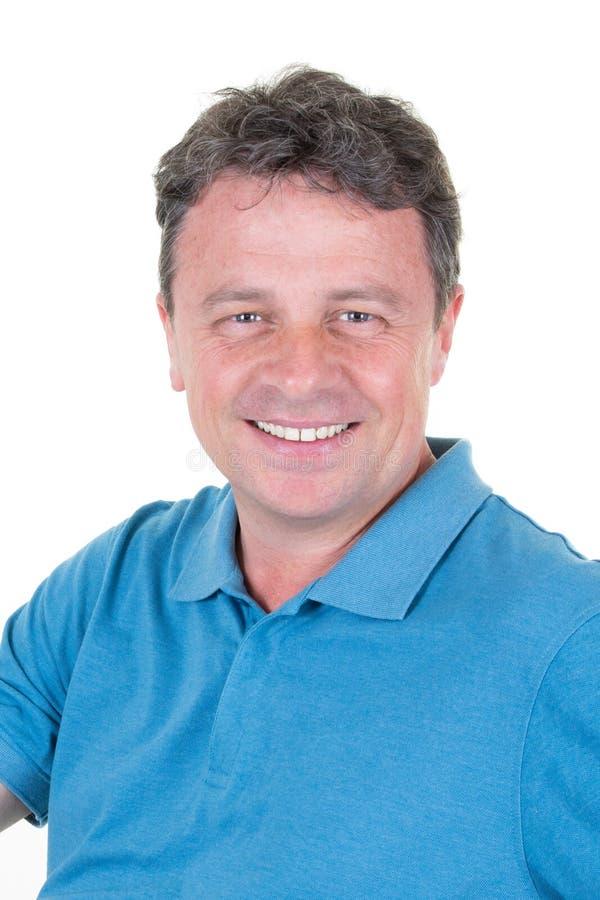 Olhos de azuis consideráveis de sorriso do homem na posição azul do polo isolados no fundo branco imagem de stock royalty free