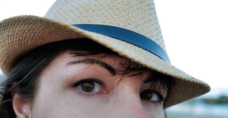 Olhos de Brown de uma jovem mulher bonita em um chapéu, close up foto de stock royalty free