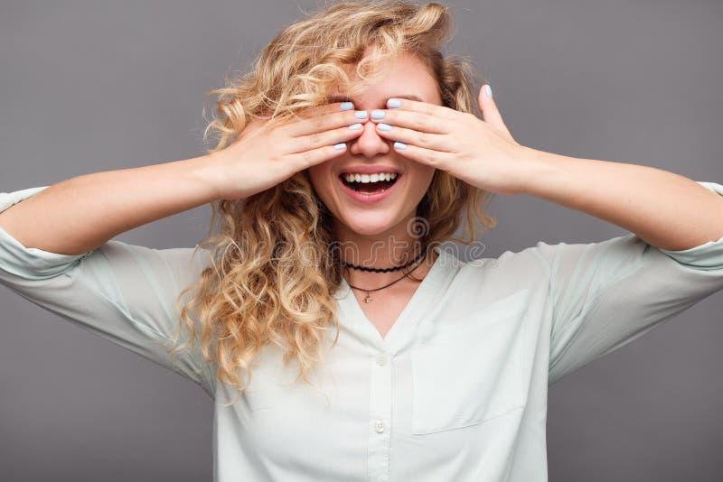 Olhos de sorriso da coberta da menina com mãos imagens de stock royalty free