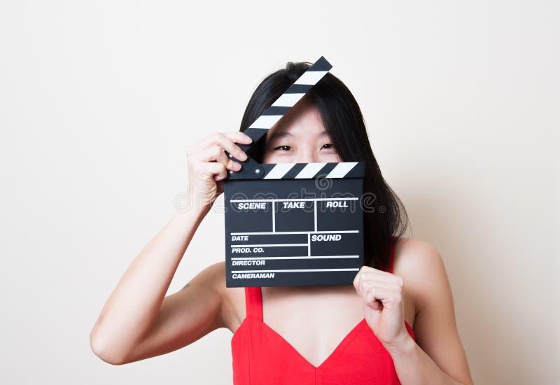 Olhos de sorriso do vestido vermelho asiático bonito novo da mulher com clapperb fotografia de stock royalty free