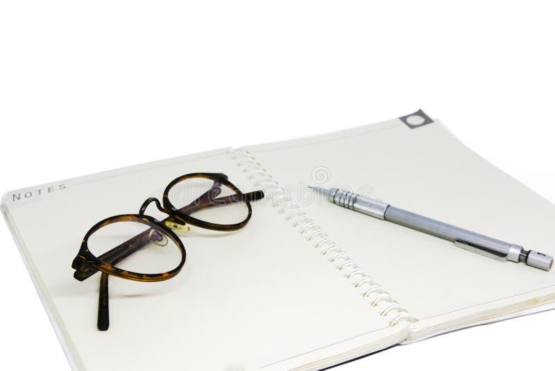 Olhos e pena pretos de vidros no caderno branco imagens de stock