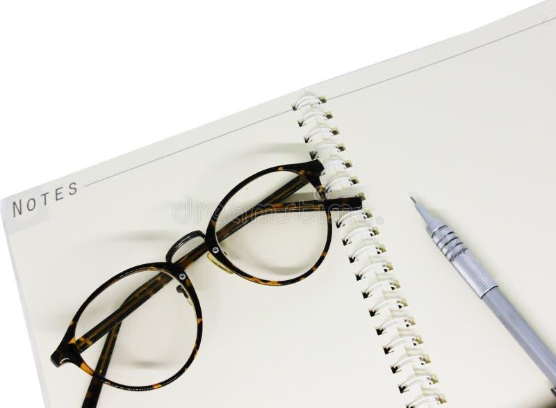 Olhos e pena pretos de vidros no caderno branco foto de stock royalty free