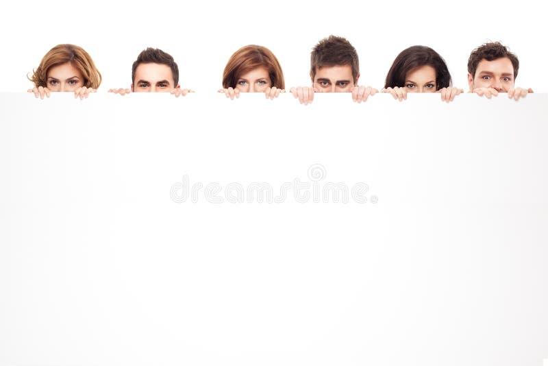 Olhos engraçados que espreitam atrás do whiteboard fotografia de stock