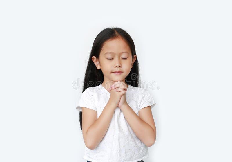 Olhos fechados linda garotinha asiática rezando isolada em fundo branco Espiritualidade e religião foto de stock royalty free