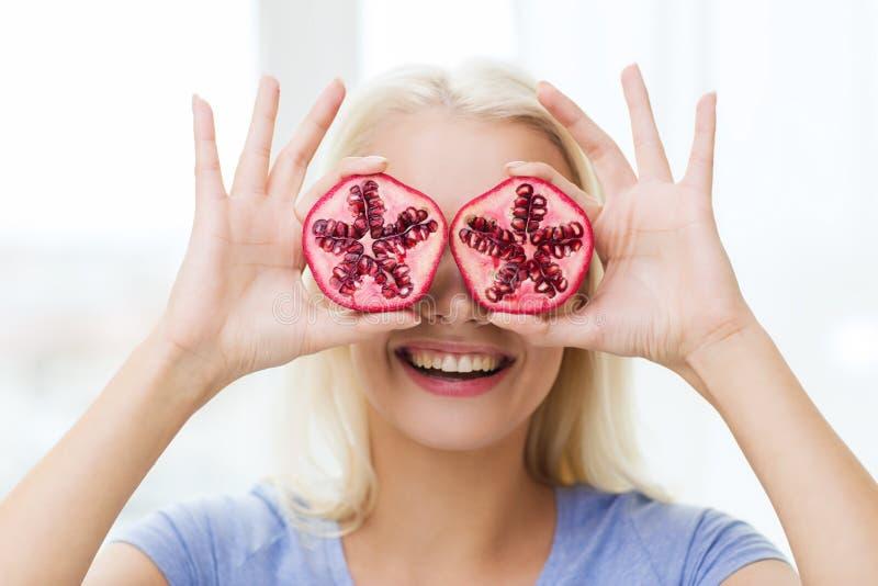 Olhos felizes da coberta da mulher com romã fotos de stock