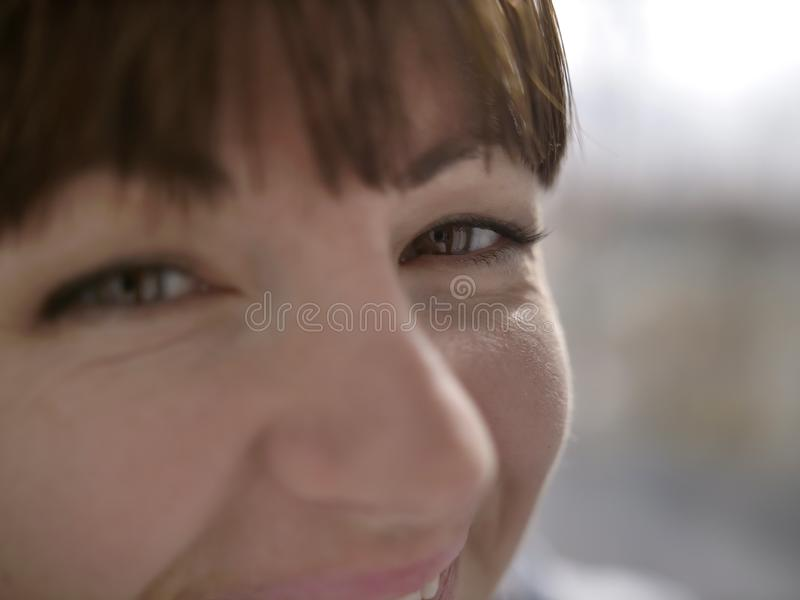 Olhos marrons felizes de uma moça, close up fotografia de stock