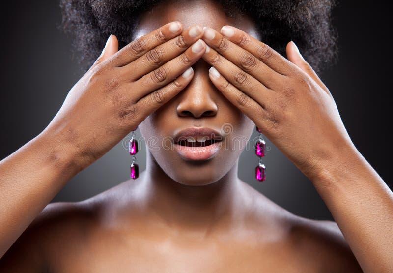 Olhos pretos da coberta da beleza com ambas as mãos imagem de stock