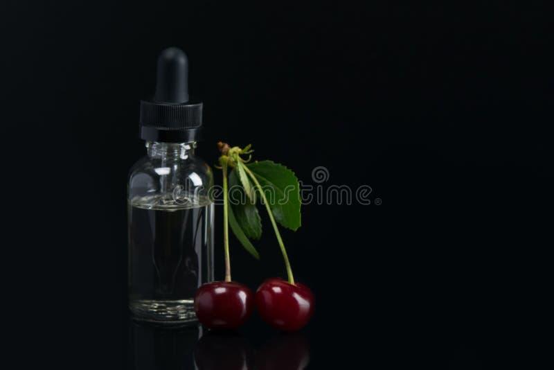 Oli dell'aroma in una latta con un erogatore, accanto alla frutta delle ciliege mature trovandosi sul fondo nero immagine stock