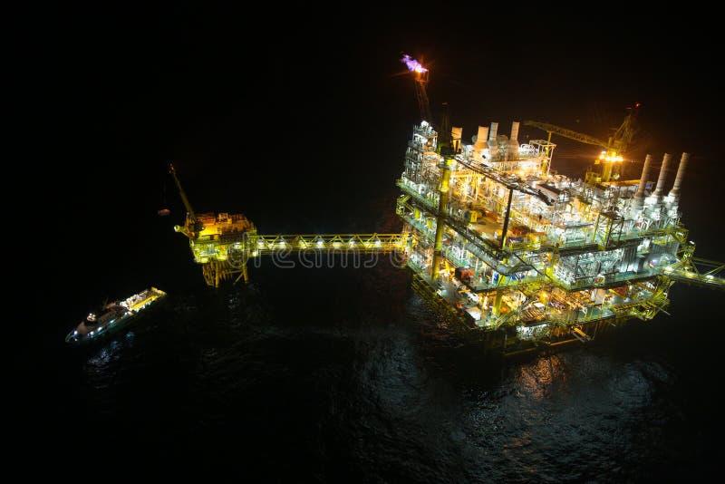 Olie en gasbouw in nachtmening Mening van de vlucht van de helikopternacht Olie en gasplatform binnen voor de kust stock fotografie
