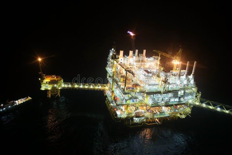 Olie en gasbouw in nachtmening Mening van de vlucht van de helikopternacht Olie en gasplatform binnen voor de kust stock foto