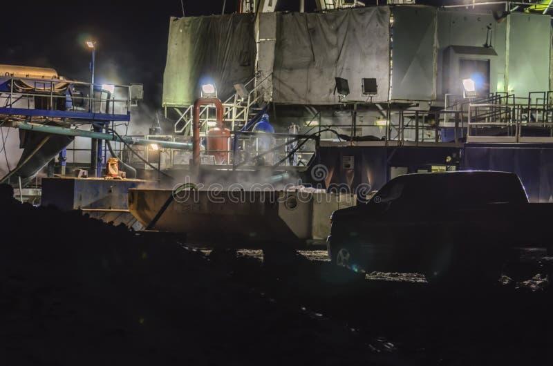 Olie het boren bij nacht stock fotografie