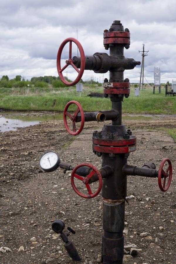 Olie kleppen en het door buizen leiden Productiebron Een natuurlijke oliebron Horizontale mening van een bron met klepanker Olie  stock afbeelding