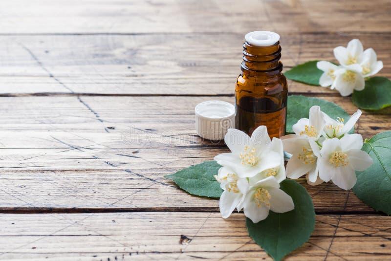 Olie van jasmijn Aromatherapy met jasmijnolie De bloemen van de jasmijn Houten achtergrond met exemplaarruimte stock foto's