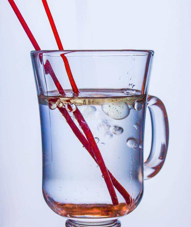 Oliedalingen in Glas Water stock afbeelding