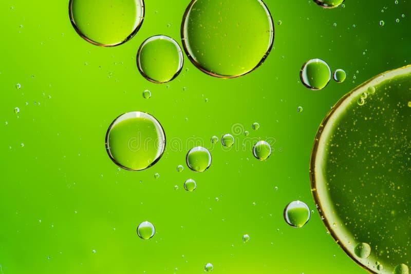 Oliedalingen in water, bellen op groene abstracte achtergrond royalty-vrije stock fotografie