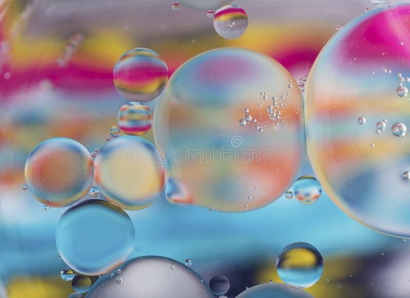 Oliedalingen in watermacro met een kleurrijke achtergrond stock foto's
