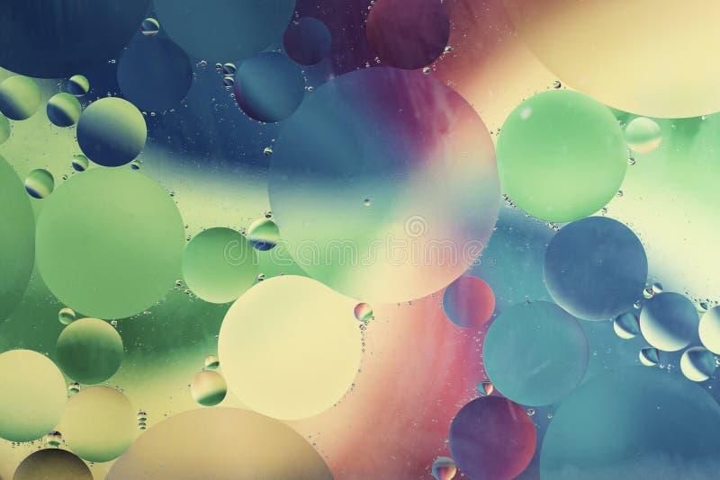 Oliedalingen in watermacro met een kleurrijke achtergrond royalty-vrije stock foto