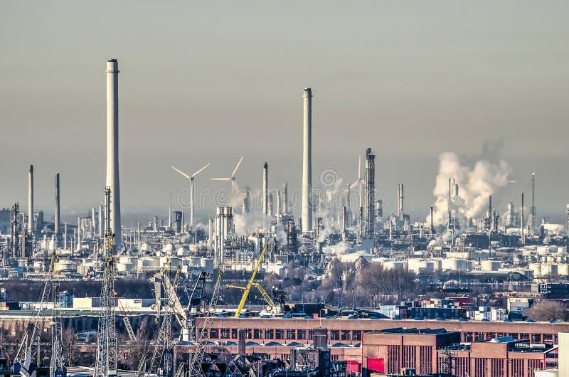 Olieraffinaderij en windturbines stock foto's