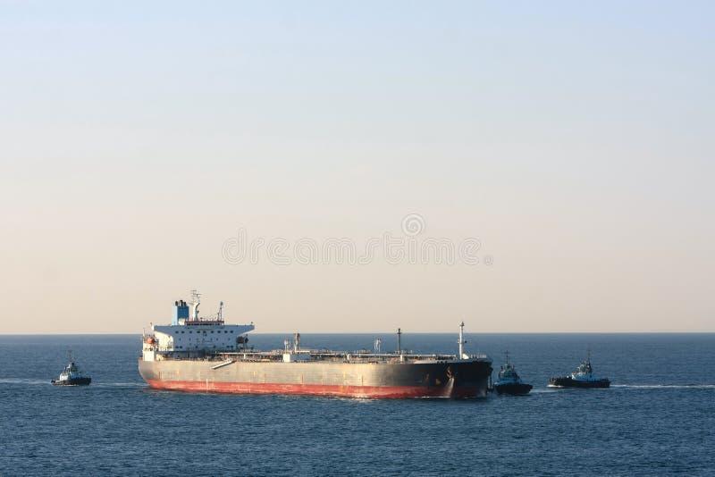 Olietankerschip op zee met drie sleepbootboten royalty-vrije stock foto