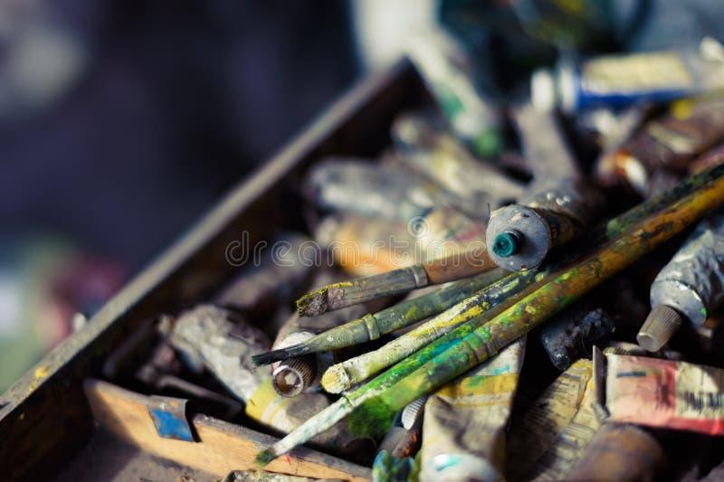Olieverven en borstels op het oude schildersezel en kleurenpalet stock foto