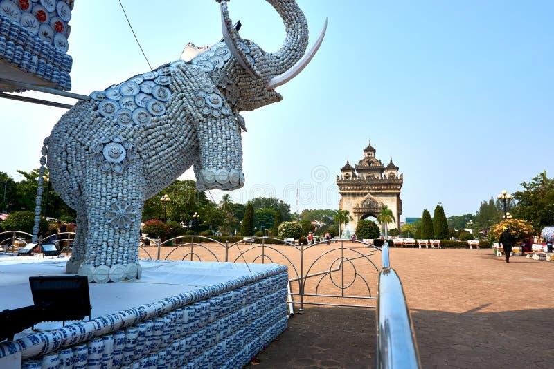 Olifantsstandbeeld uit koppen en platen naast het Oriëntatiepunt van Patuxai Victory Monument The One Attractive van Vientiane-St stock foto's