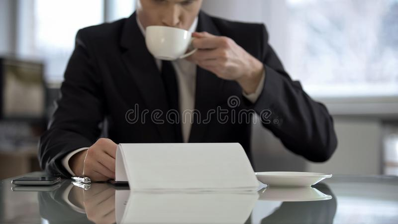 Oligarch drinking coffee in his office and reading text of contract for signing. Stock photo stock image