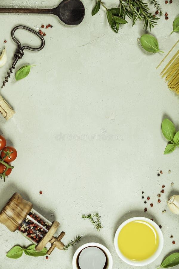 Olijfolie, balsemieke azijn, zout, peper, kruiden, deegwaren, tomaten op concrete achtergrond royalty-vrije stock afbeeldingen